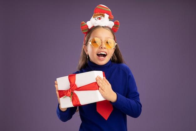 赤いネクタイと面白いクリスマスの縁に赤いネクタイと面白いクリスマスの縁の青いタートルネックの少女は、紫色の壁の上に立って幸せで陽気な顔に笑顔でプレゼントを持っています