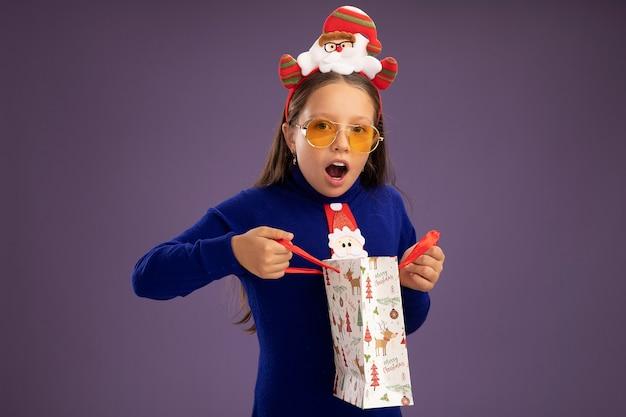 Маленькая девочка в синей водолазке с красным галстуком и забавной рождественской оправой на голове держит бумажный пакет с рождественским подарком счастливая и удивленная, стоя над фиолетовой стеной