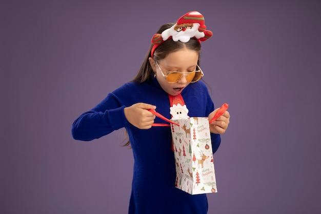 赤いネクタイと面白いクリスマスの縁の青いタートルネックの少女は、紫色の背景の上に立って驚いて中を見てクリスマスの贈り物と紙袋を保持しています