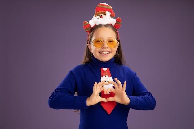 赤いネクタイと頭に面白いクリスマスの縁を持つ青いタートルネックの少女は、紫色の背景の上に立っている指で元気にハートのジェスチャーを作って笑顔のカメラを見て