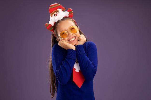 赤いネクタイと面白いクリスマスの縁の青いタートルネックの少女は、紫色の背景の上に幸せで前向きに立っている顔に笑顔でカメラを見て