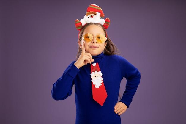 赤いネクタイと紫色の背景の上に立っている顔に笑顔でカメラを見て頭に面白いクリスマスの縁を持つ青いタートルネックの少女
