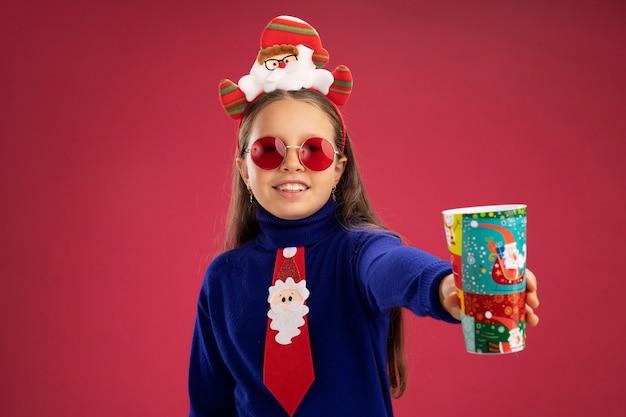 赤いネクタイと頭に面白いクリスマスの縁を持つ青いタートルネックの小さな女の子は、カラフルな紙コップを元気に幸せで前向きな笑顔を示しています