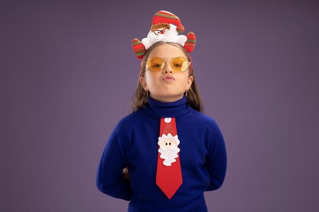 赤いネクタイと紫色の壁の上に立っている自信を持って表情と頭に面白いクリスマスの縁を持つ青いタートルネックの少女