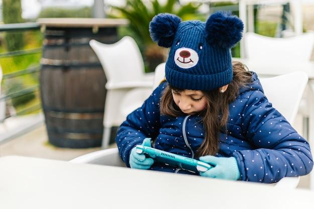 Маленькая девочка в синей зимней одежде, играя на портативной консоли на открытом воздухе