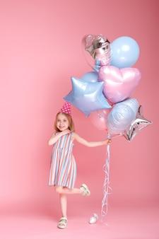 분홍색 표면에 풍선 모자 춤에 어린 소녀