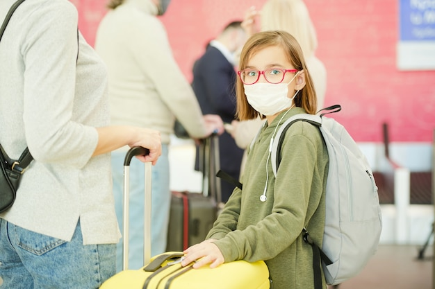 Маленькая девочка в повседневной одежде, очках и защитной маске стоит перед камерой против путешественников, ожидающих своей очереди на проверку в аэропорту