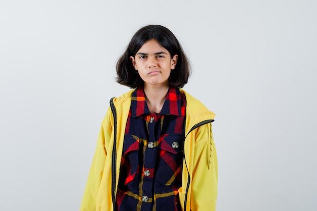 체크 셔츠를 입은 어린 소녀, 재킷이 입술을 구부리고 생각에 잠긴 모습, 전면 전망.