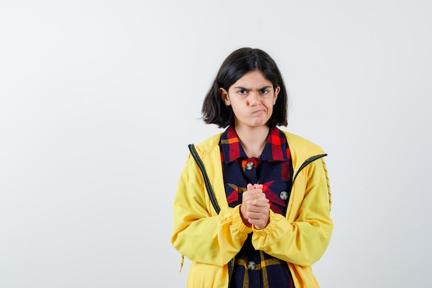 체크 셔츠를 입은 어린 소녀, 깍지 낀 손을 잡고 사려깊은 앞모습을 바라보면서 입술을 구부린 재킷.