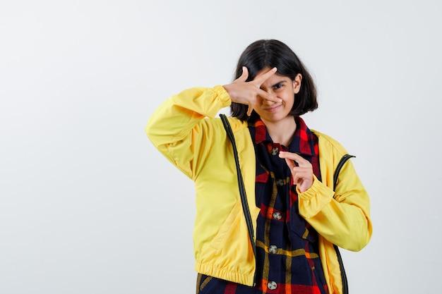 チェックシャツ、指を通して見て自信を持って見えるジャケットの少女