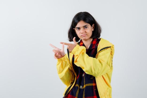 체크 셔츠를 입은 어린 소녀, 재킷은 왼쪽을 가리키고 자신감이 있어 보이는 전면 전망입니다.
