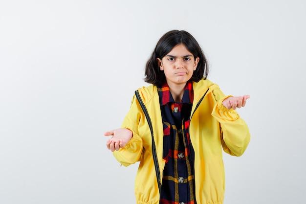 チェックシャツ、無力なジェスチャーを示し、絶望的に見えるジャケットの少女