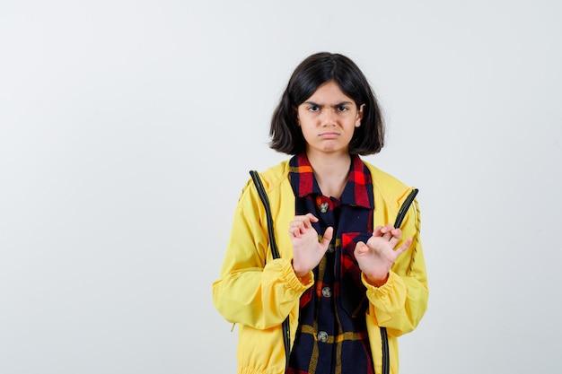 チェックシャツを着た少女、降伏のジェスチャーで手のひらを示し、絶望的に見えるジャケット