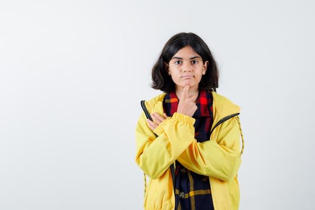 チェックシャツを着た少女、思考ポーズで立っているジャケット、思慮深く見える、正面図。