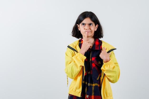 チェックシャツ、思考ポーズで立って思慮深く見えるジャケットの少女