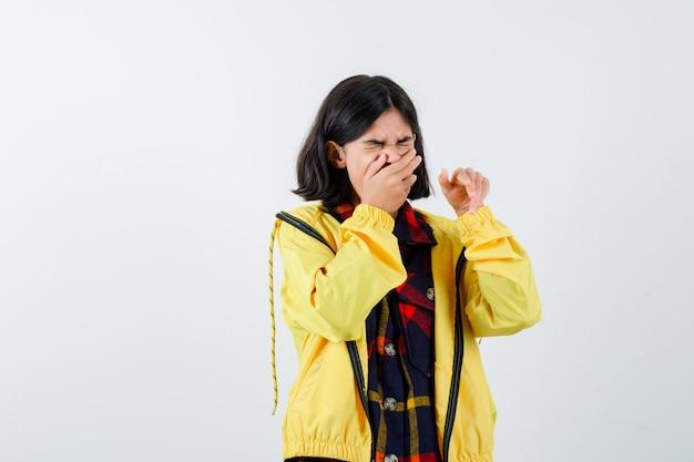 チェックシャツ、あくびをして眠そうなジャケットを着た少女