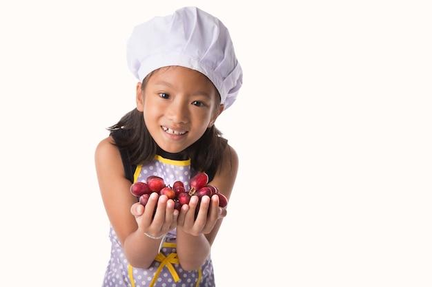 白い背景に隔離された手でブドウや果物を保持しているシェフのドレスの少女