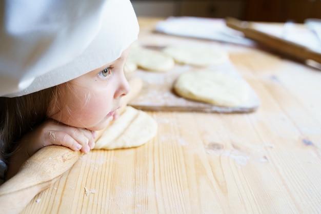 Маленькая девочка в кепке шеф-повара лепит тесто скалкой