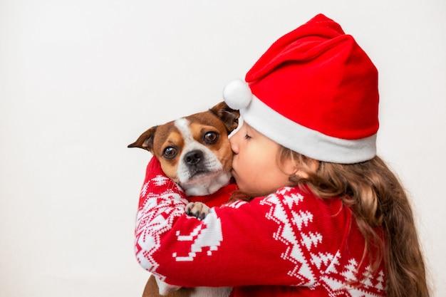 크리스마스 재킷과 모자 키스 개에 어린 소녀