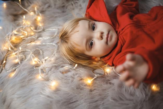 Маленькая девочка в новогоднем комбинезоне с праздничным настроением лежит на кровати вокруг светящейся гирлянды