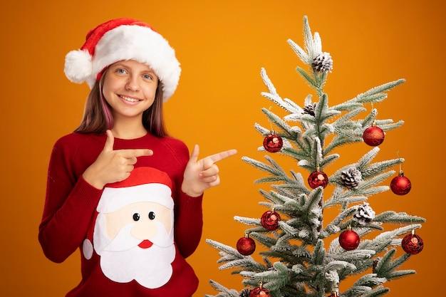 크리스마스 스웨터와 산타 모자에 어린 소녀 행복하고 놀란 오렌지 배경 위에 서있는 크리스마스 트리에서 검지 손가락으로 유쾌하게 가리키는 미소