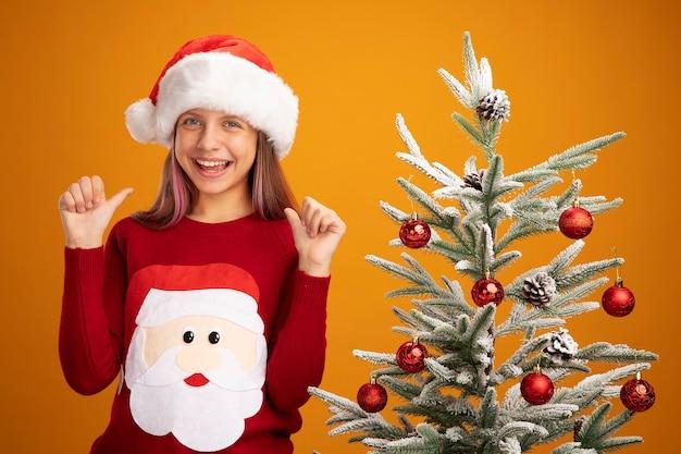 クリスマスのセーターとサンタ帽子の少女は、オレンジ色の背景の上のクリスマスツリーの横に立って親指を元気に見せて元気に笑顔で幸せで驚きました