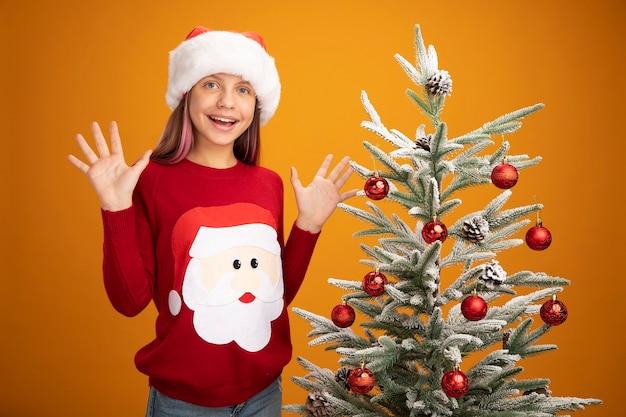 クリスマスのセーターとサンタ帽子の少女は、オレンジ色の背景の上のクリスマスツリーの横に元気に立って笑顔で幸せで驚きました