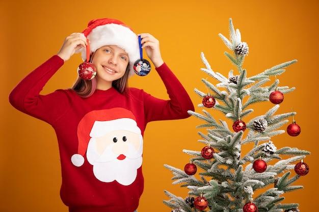 Маленькая девочка в рождественском свитере и шляпе санта-клауса держит шары, глядя в камеру, улыбаясь, стоя рядом с елкой на оранжевом фоне