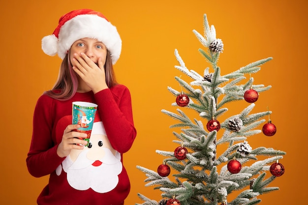 크리스마스 스웨터와 산타 모자에 어린 소녀 오렌지 배경 위에 크리스마스 트리 옆에 서있는 손으로 카메라를 행복하고 놀란 덮고 입을보고 다채로운 종이 컵을 들고