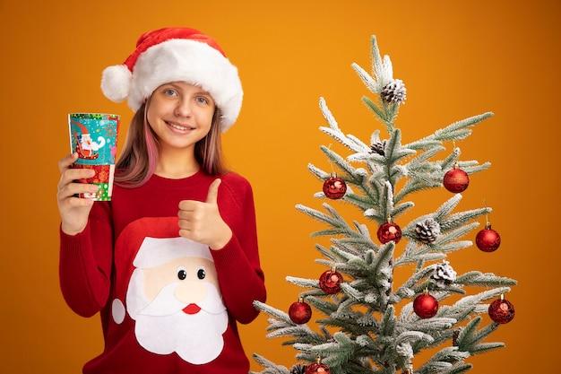 크리스마스 스웨터와 산타 모자에 어린 소녀 오렌지 배경 위에 크리스마스 트리 옆에 서 엄지 손가락을 보여주는 웃 고 다채로운 종이 컵을 들고