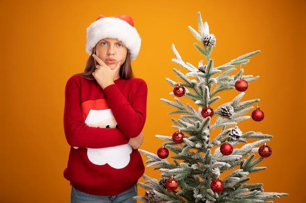 크리스마스 스웨터와 산타 모자에 어린 소녀 오렌지 배경 위에 크리스마스 트리 옆에 서 턱 생각에 손으로 카메라를 찾고