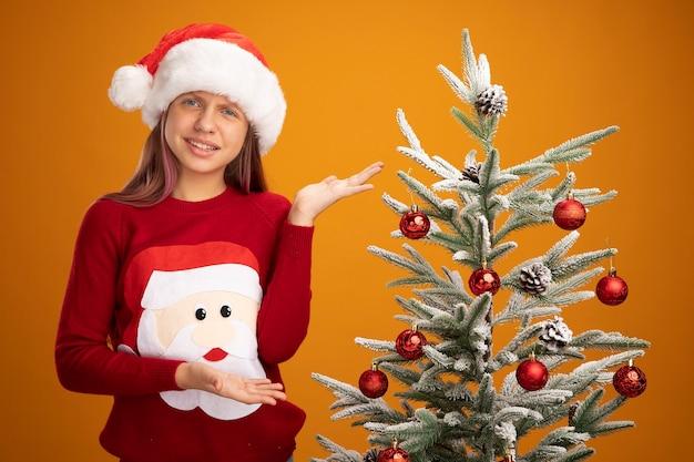 クリスマスのセーターとサンタの帽子をかぶった少女がクリスマスツリーの横に立って、オレンジ色の背景に混乱して笑っている