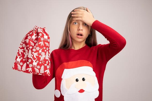 Маленькая девочка в рождественском свитере держит красную сумку санта-клауса с подарками, глядя в камеру, пораженная рукой на лбу, стоящей на белом фоне