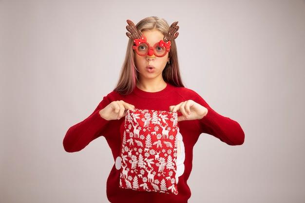 白い背景の上に立って驚いたカメラを見て贈り物とサンタの赤いバッグを保持している面白いパーティーメガネを身に着けているクリスマスセーターの少女