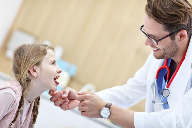 Маленькая девочка в клинике осматривается ларингологом