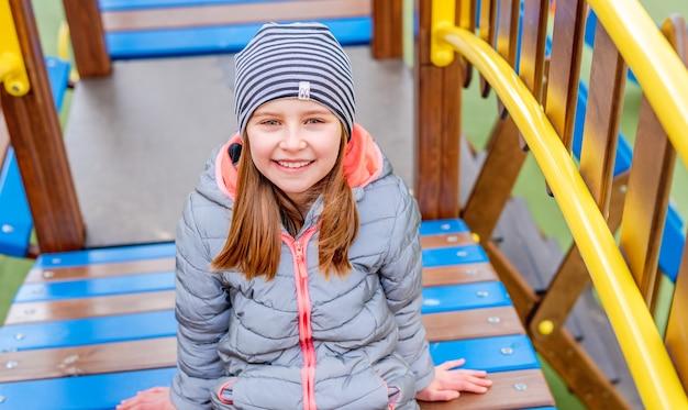 Маленькая девочка в пальто и шляпе, сидя на деревянной красочной детской площадке в осеннее время