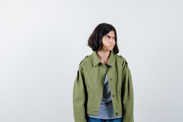 코트, 티셔츠, 청바지를 입은 어린 소녀가 시선을 돌리고 수심에 찬 앞모습을 바라보면서 입술을 구부립니다.