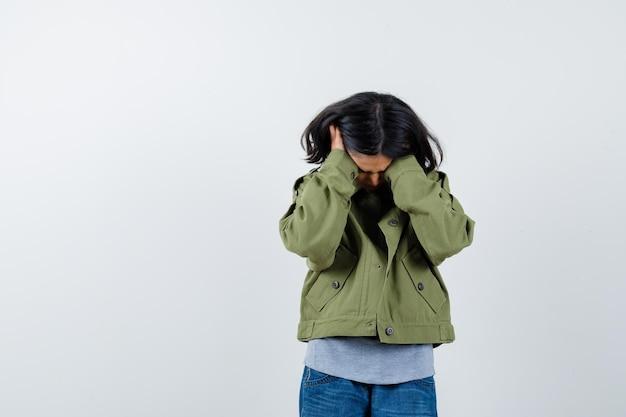 코트, 티셔츠, 청바지를 입은 어린 소녀가 귀에 손을 대고 피곤해 보이는 앞모습.