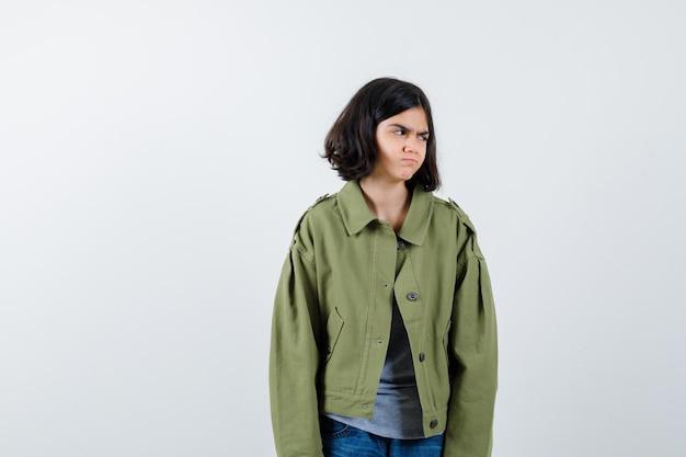 코트, 티셔츠, 청바지를 입은 어린 소녀가 멀리 바라보고 그리운 앞모습을 보고 있습니다.