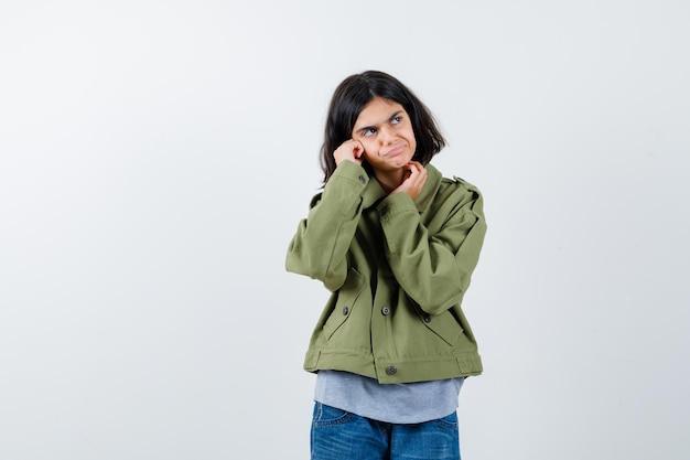 コート、tシャツ、ジーンズで考えながら物思いにふける、正面から見ている少女。