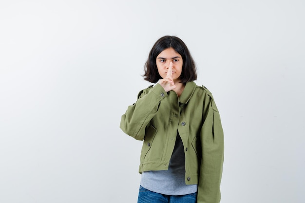 Маленькая девочка в пальто, футболке, джинсах показывает жест пистолета возле носа и злобно смотрит, вид спереди.