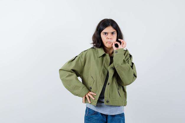 コート、tシャツ、ジーンズで大丈夫なジェスチャーを示し、自信を持って見える、正面図の少女。
