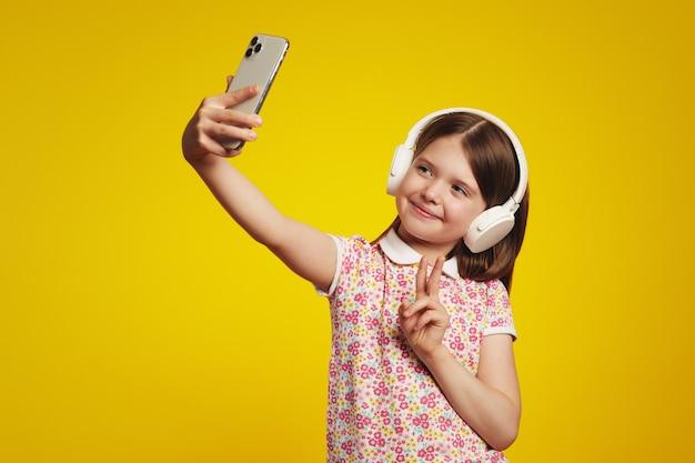 Маленькая девочка в красочной рубашке поло, делающей селфи во время прослушивания музыки