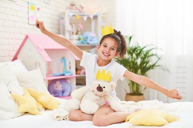 Маленькая девочка в короне, сидя на кровати в детской комнате и обнимая плюшевого мишку
