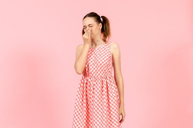 Маленькая девочка в милом ярком платье закрыла нос на розовом