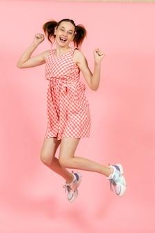 Маленькая девочка в милом ярком платье счастливо прыгает на розовом