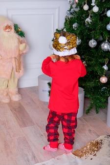 かわいいパジャマ姿の少女がクリスマスツリーを飾る