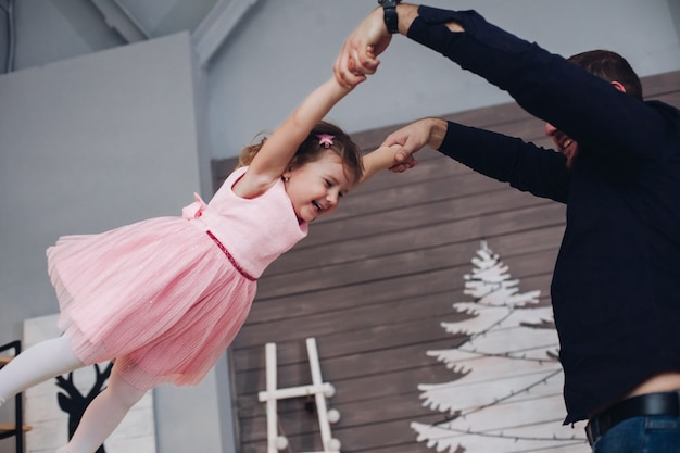 かわいいピンクのドレスを着た小さな女の子は、クリスマスの雰囲気の中で彼女の父親ととても楽しいです。