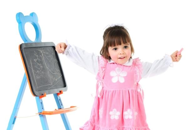 手を上げて子供のボードの近くでポーズをとってかわいいピンクのドレスの少女