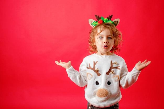 Маленькая девочка в оленьих рогах на красном фоне, рождество, новый год